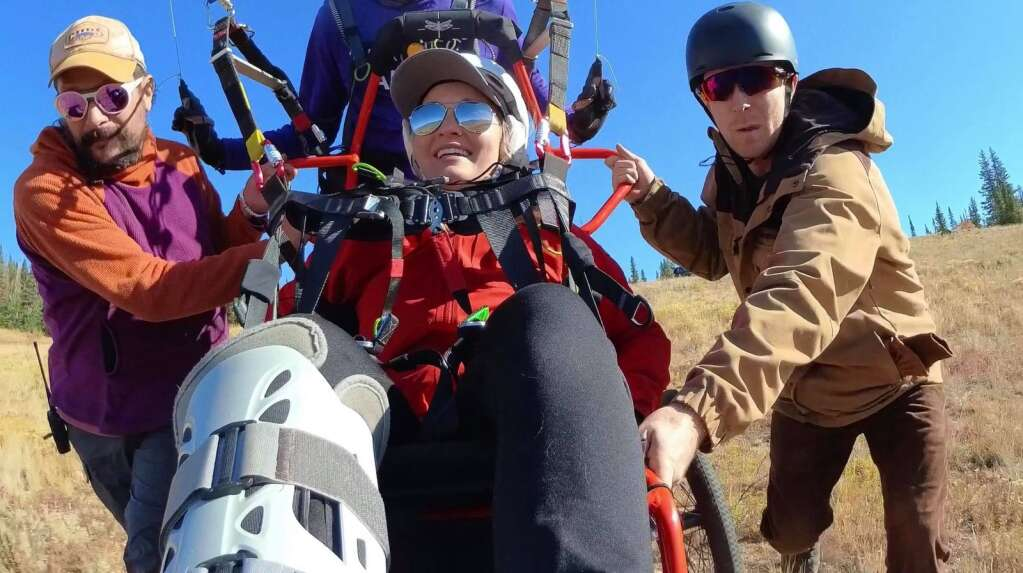 With the aid of a couple of friends at left and right, Charlie Martin (not pictured) pilots adaptive flier Danelle Herra in a Project Airtime tandem wheelchair from Williams Peak near Green Mountain Reservoir on Sept. 18. | Charlie Martin/Courtesy photo