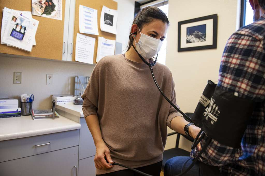 Registered nurse Maria McHale checks a coworkers blood pressure in an exam room at MidValley Family Practice in Basalt on Dec. 24, 2020. (Kelsey Brunner/The Aspen Times)