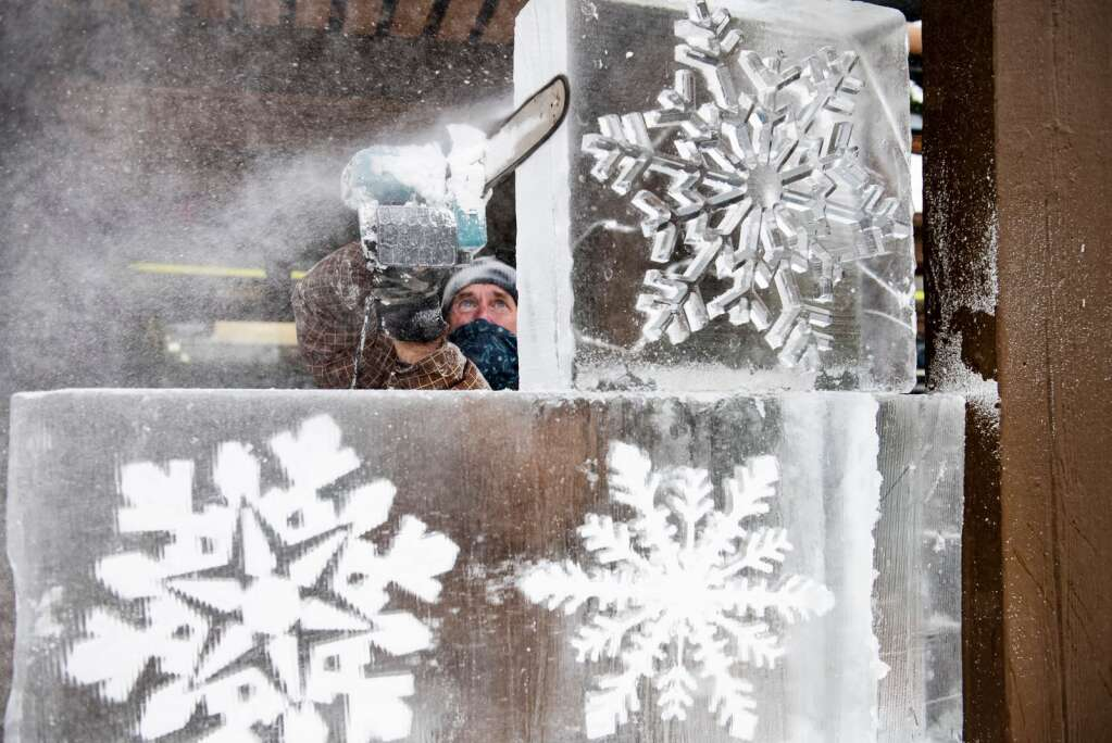 Multimedia artist Thomas Barlow constructs a chainsaw ice sculpture in Snowmass Mall on Wednesday, Dec. 16, 2020. The intricate snowflakes were created using a computer. Barlow will be creating work twice a month through March, tentatively. Barlow is planning to create a mammoth, an interactive gondola cab, and a logo at The Collective with different words and a bench. (Kelsey Brunner/The Aspen Times)