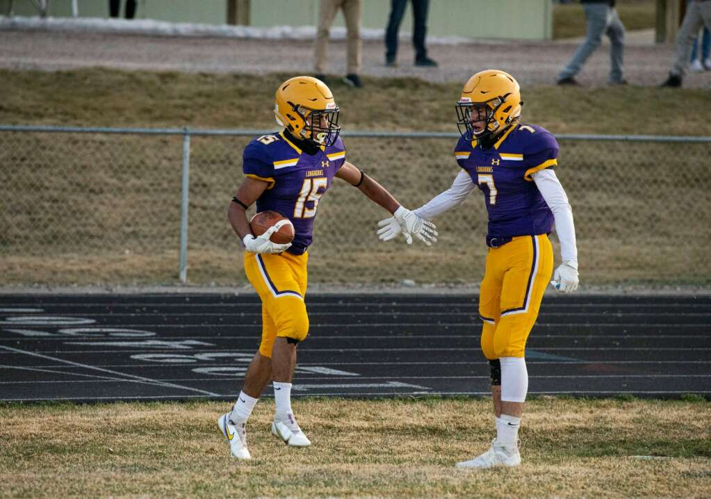 Basalt High School's wide receiver and captain Rulbe Alvarado high-fives teammate Wilson Maytham after intercepting a pass by Glenwood Springs during the first half of the game on Friday, April 9, 2021. (Kelsey Brunner/The Aspen Times)