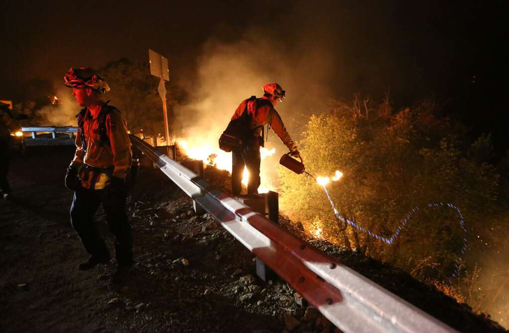 Cal Fire firefighters initiate a firing procedure to back burn fire fuel to the front lines of the Jones Fire Tuesday morning along Highway 49.   Photo: Elias Funez
