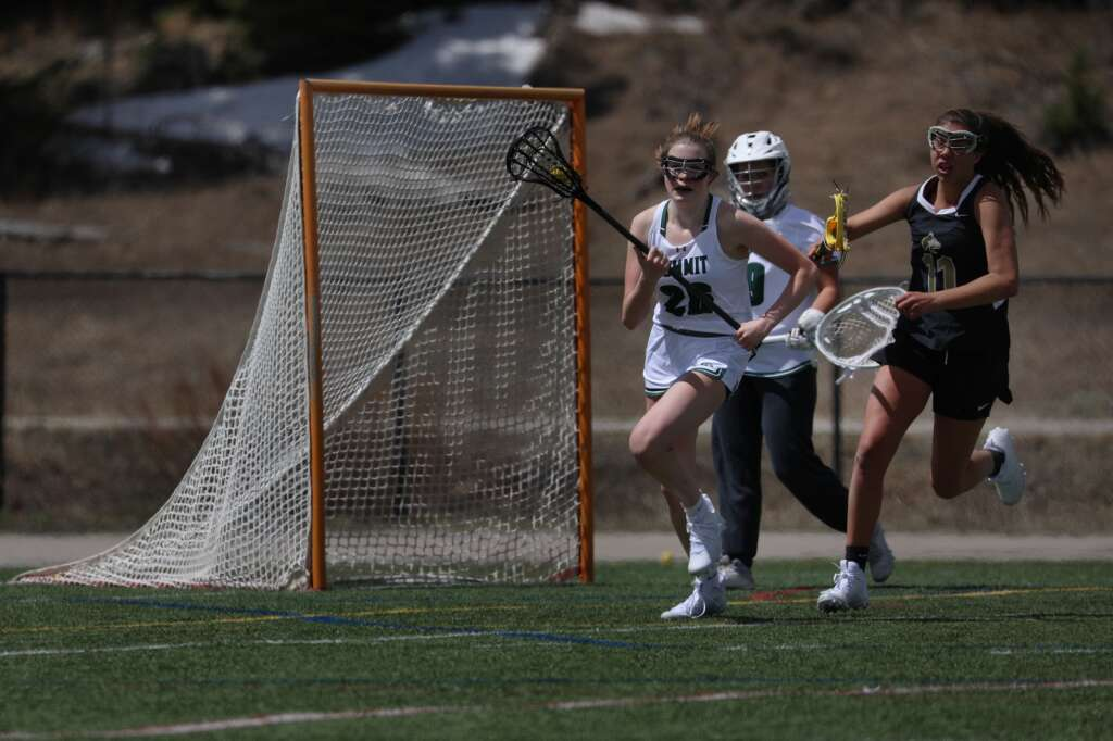 Summit High School junior Logan Reid cradles possession in front of the Tigers net against Battle Mountain during the Tigers girls varsity lacrosse team's season opener vs. Battle Mountain on May 8 at Tiger Stadium in Breckenridge. | Photo by Ashley Low / Ashley Low Photography