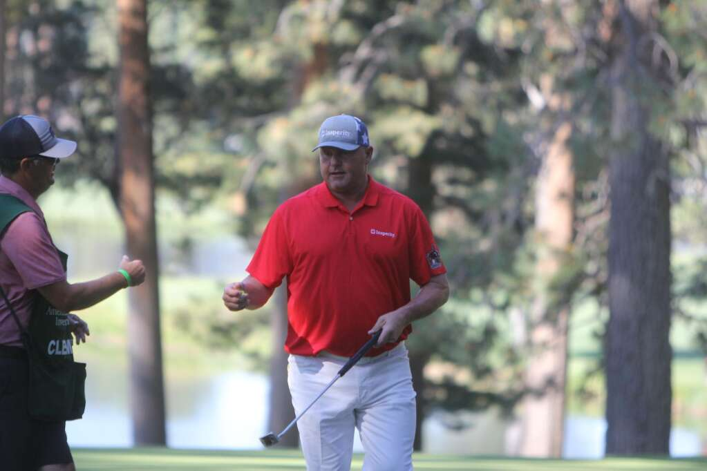 Roger Clemens fist bumps his caddy.