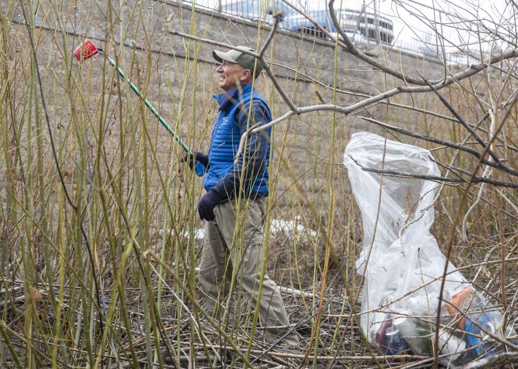 Chris Cherniak picks up trash near Poison Creek along the Rail Trail Saturday morning during an Earth Day cleanup effort organized by Recycle Utah. Cherniak, a board member of Recycle Utah, picked up a variety of pieces of litter ranging from plastic bags and beer cans to face masks and styrofoam pieces from the nearby demolition for the arts and culture district. (Tanzi Propst/Park Record)