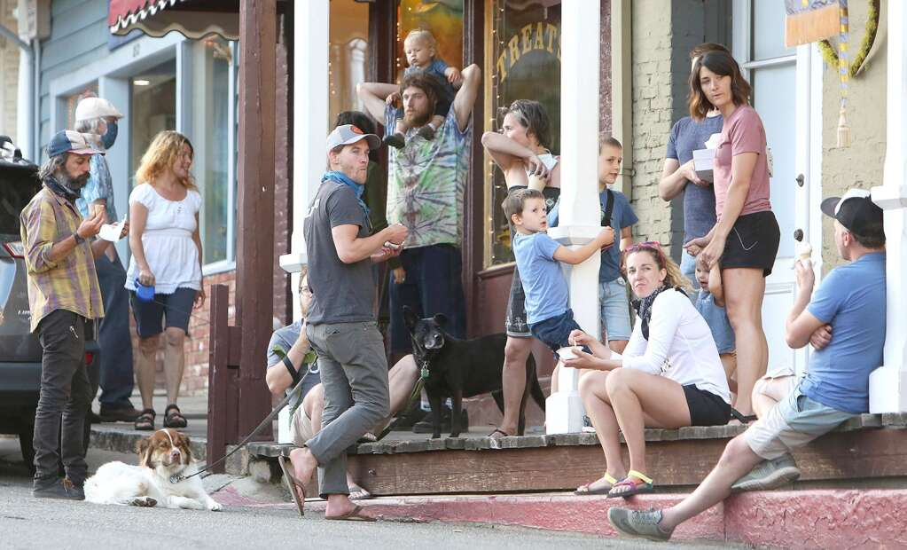 Folks gather on the boardwalk in front of Treats in Nevada City during a pleasant day in late May. Treats is also open after being closed due to the coronavirus shutdowns. | Photo: Elias Funez