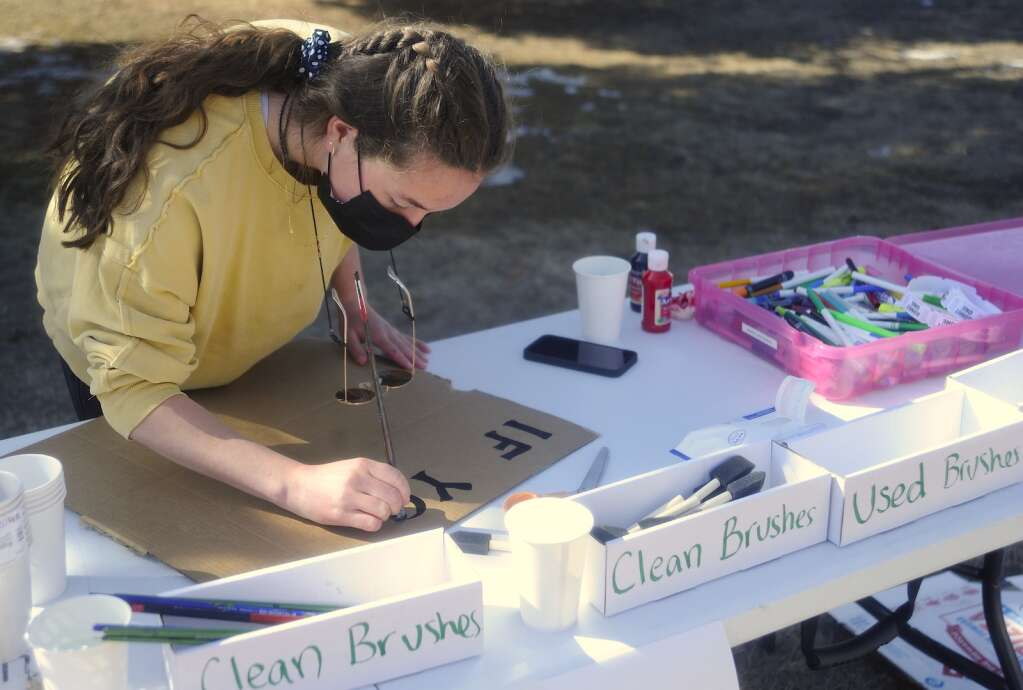 Courtney Vargas, 17, paints a sign at a Climate Action Rally at the Routt County Courthouse Lawn on Friday afternoon. (Photo By Shelby Reardon)