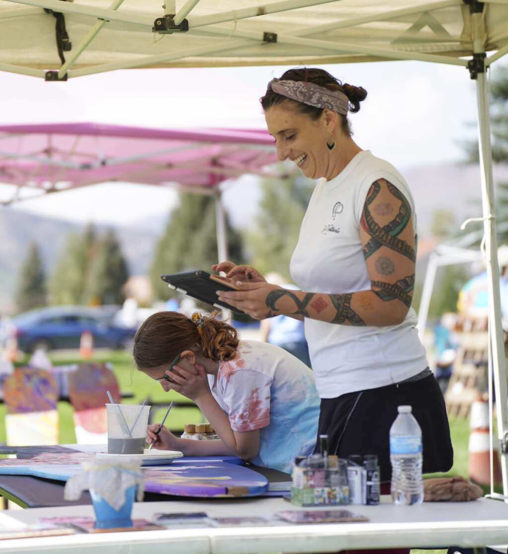 Nico Iona and her daughter Ruby team up to paint a fish panel on Saturday, Sept. 4, 2021, at the Art in the Park festival in Granby.   Eli Pace / Sky-Hi News