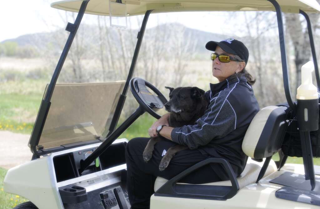 Steamboat Springs girls golf head coach Shannon Hanley watches a player while her dog, Lady, relaxes on her lap at the Bulldog Invite in Craig on Tuesday afternoon. (Photo by Shelby Reardon)