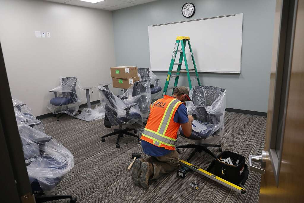 Tyler Beh, a school employee, assembles furniture in the administrative offices at the new Sleeping Giant School. (Photo by John F. Russell)