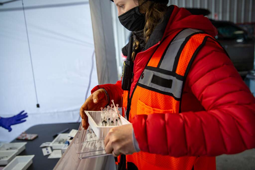 Lauren Gilbert carries containers of syringes containing the COVID-19 vaccine on Saturday, Feb. 13, 2021, during a vaccine drive at the bus depot in Frisco, Colo. Photo by Liz Copan / Studio Copan