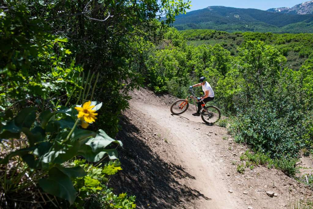 A mountain biker makes a turn on Viewline Trail in Sky Mountain Park in Snowmass on Monday, June 14, 2021. The high heat is forecasted to continue through the week with temperatures in the high 80s and low 90s with a thunderstorm expected on Saturday. (Kelsey Brunner/The Aspen Times)
