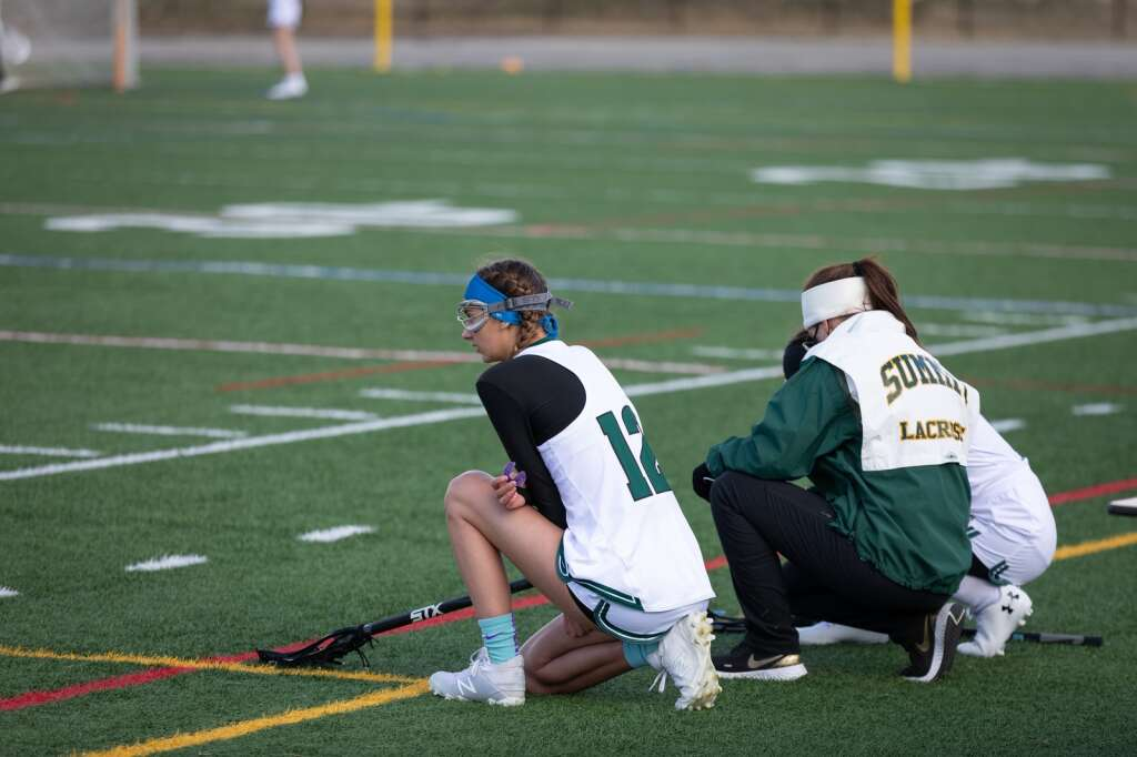 Katherine Costello (left) kneels on the sideline during the Summit High School varsity girls lacrosse team's 14-4 loss to Eagle Valley at Summit High School in Breckenridge on Tuesday, May 11, 2021. | Photo by Lucas Herbert / Lucas Herbert Media