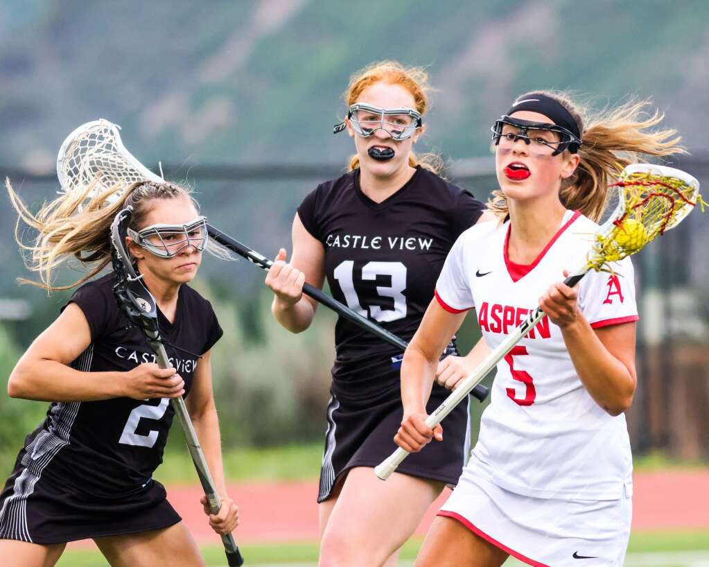 Aspen High School senior Kylie Kenny, right, brings the ball upfield in the girls lacrosse game against Castle View in the Class 4A state quarterfinals on Saturday, June 19, 2021, on the AHS turf. The Sabercats won, 10-9. Photo by Austin Colbert/The Aspen Times.
