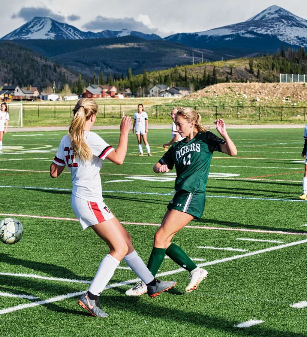 Summit's Kelly Duffey (right) vies for possession against Glenwood Springs during the Tigers' 4-1 loss to the Demons at Tiger Stadium in Breckenridge on Tuesday. | Photo by Joel Wexler / Rocky Mountain Photography