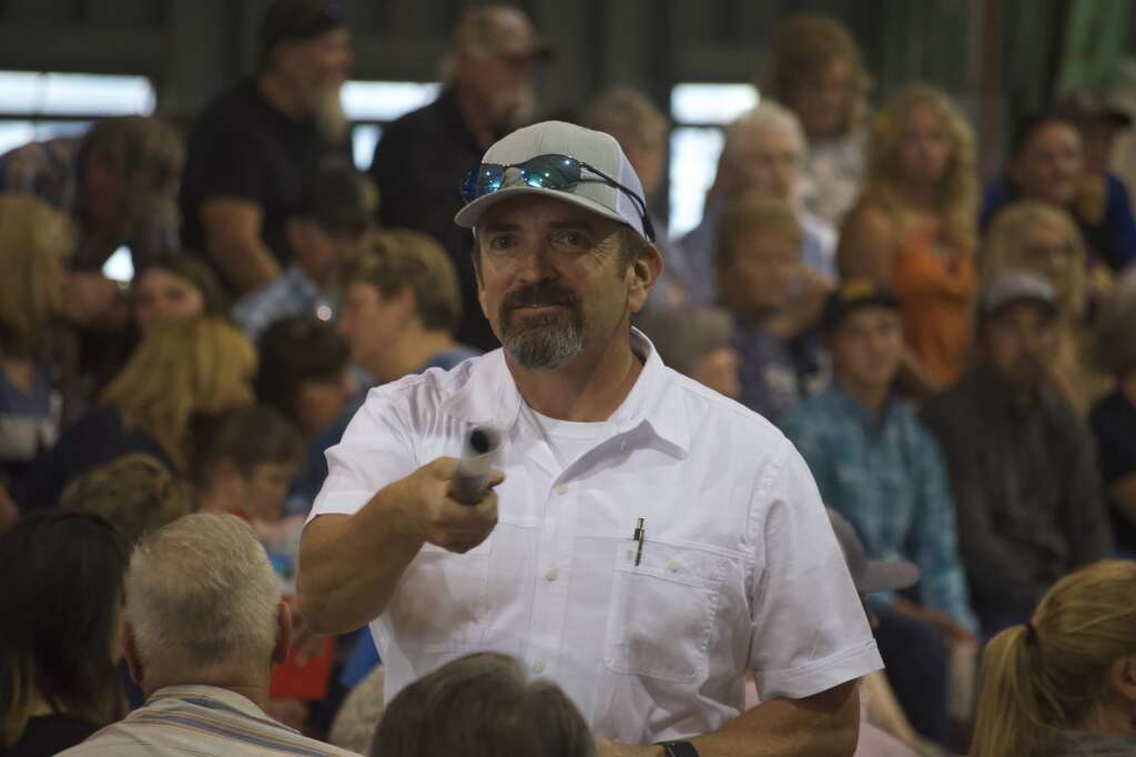 Auctioneer's assistants encourage members of the crowd to bid on livestock at the Moffat County Fair livestock auction Saturday evening. | Cuyler Meade / Craig Press