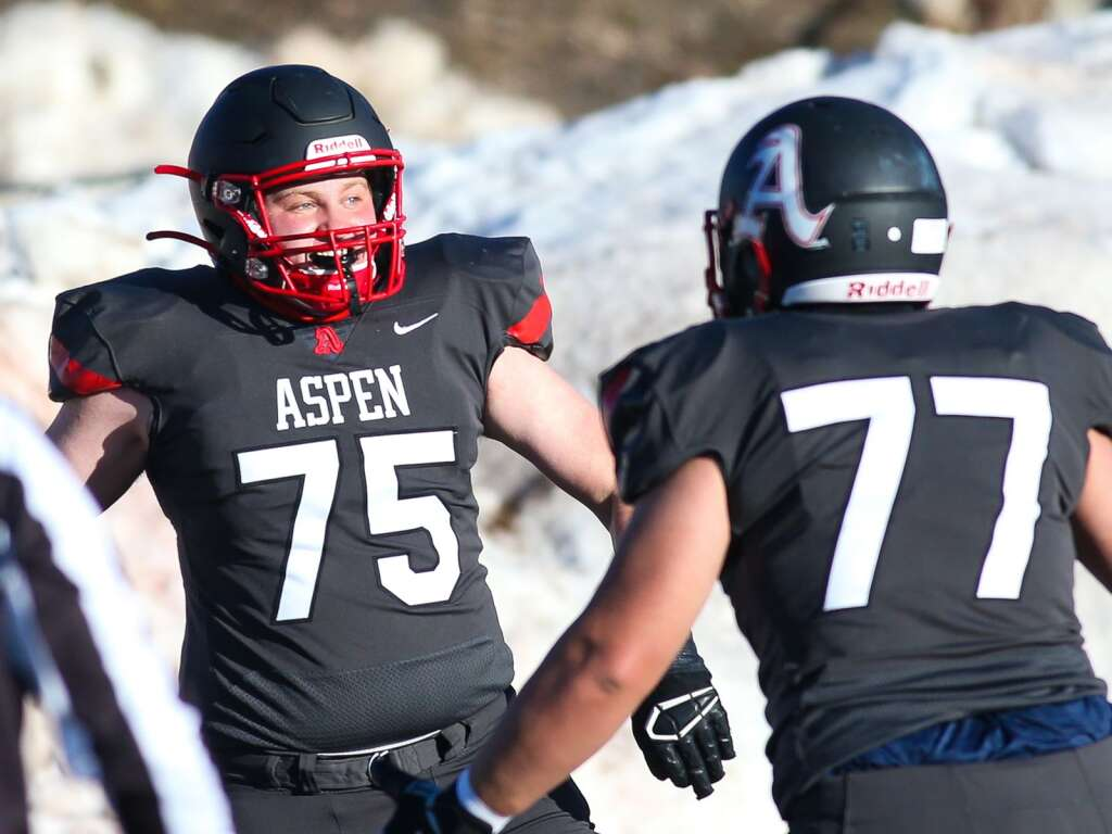 Aspen High School football's Zach Small, left, celebrates a team touchdown with Ahmed Hmani against Montezuma-Cortez on Friday, April 2, 2021, on the AHS turf. (Photo by Austin Colbert/The Aspen Times)