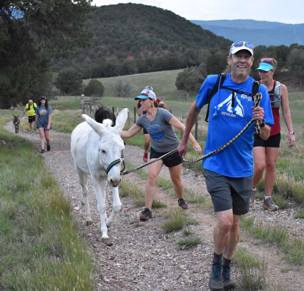 The Post Independent's John Stroud leads Charleston along on the Sutey Ranch Trail during the Independence Run & Hike burro run on Aug. 26, 2021. | Tami Stroud/Courtesy photo