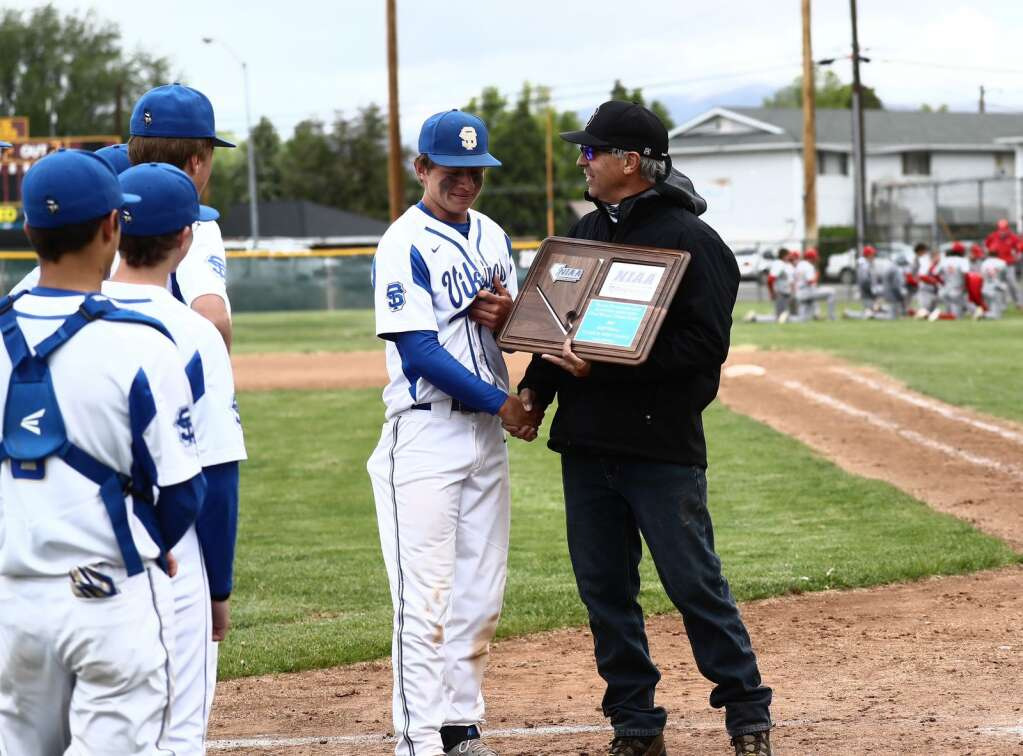 Andrew Lehmann receives the championship plaque from an NIAA official.