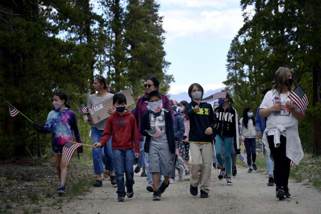 Upper Blue Elementary School fourth graders, left to right, Ava Busnardo, Nicholas George, Yahir Oliera, Jaxson Zimsky, and Jacquelyn Dohner, carry U.S. flags as they lead their classmates through Valley Brook Cemetery in Breckenridge on Friday, May 28. The students placed flags at the graves of veterans throughout the cemetery in preparation for Memorial Day. | Jason Connolly / Jason Connolly Photography