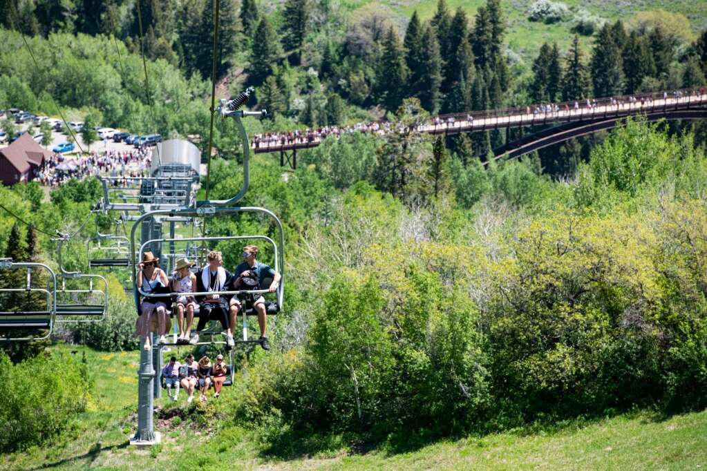 Aspen High School graduates ride up the Tiehack Lift and walk across the bridge after the commencement ceremony on Saturday, June 5, 2021. (Kelsey Brunner/The Aspen Times)