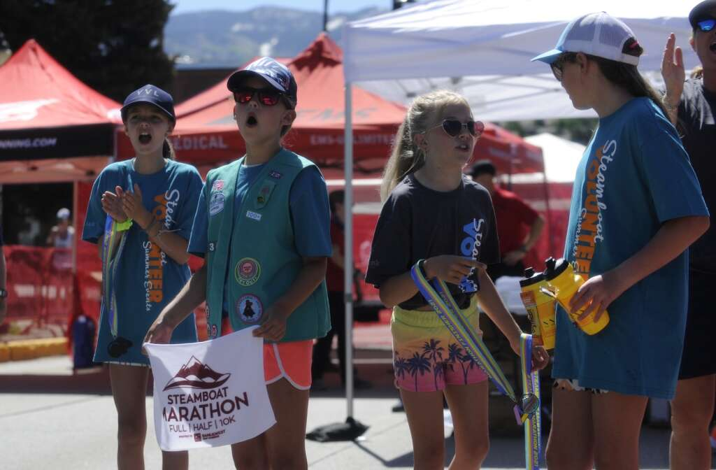 Juniors from the Steamboat Springs girl scout troop cheer on runners and hand out medals, cool towels and water at the finish line of the Steamboat Marathon on Sunday morning. (Shelby Reardon)