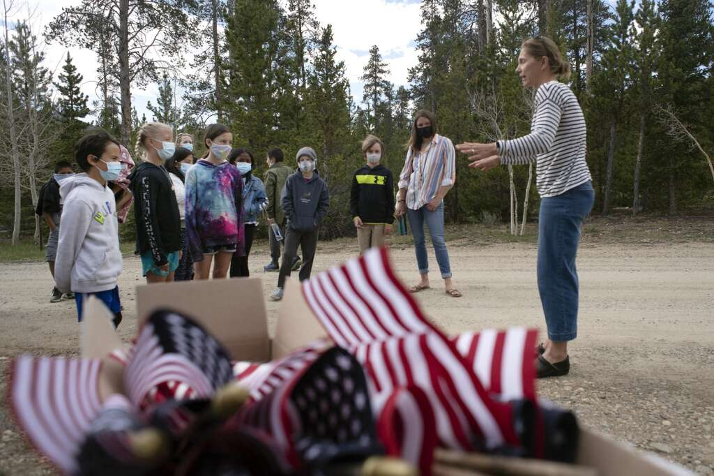 Fourth graders from Upper Blue Elementary School listen as Larissa O'Neil, executive director of the Breckenridge Heritage Alliance, speaks to them during a field trip to Valley Brook Cemetery in Breckenridge on Friday, May 28. The students placed U.S. flags at the graves of veterans throughout the cemetery in preparation for Memorial Day. | Jason Connolly / Jason Connolly Photography