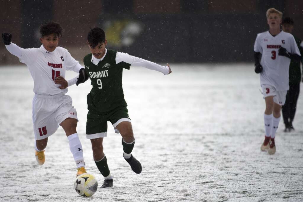 Summit High senior captain midfielder Ivan Gallardo Gutierrez battles for the ball against Glenwood Springs Demon Christopher Contreras during a snowy senior night match at Climax Molybdenum Field at Tiger Stadium on April 15, 2021. The Tigers defeated the Demons 4-0. | Photo by Jason Connolly / Jason Connolly Photography