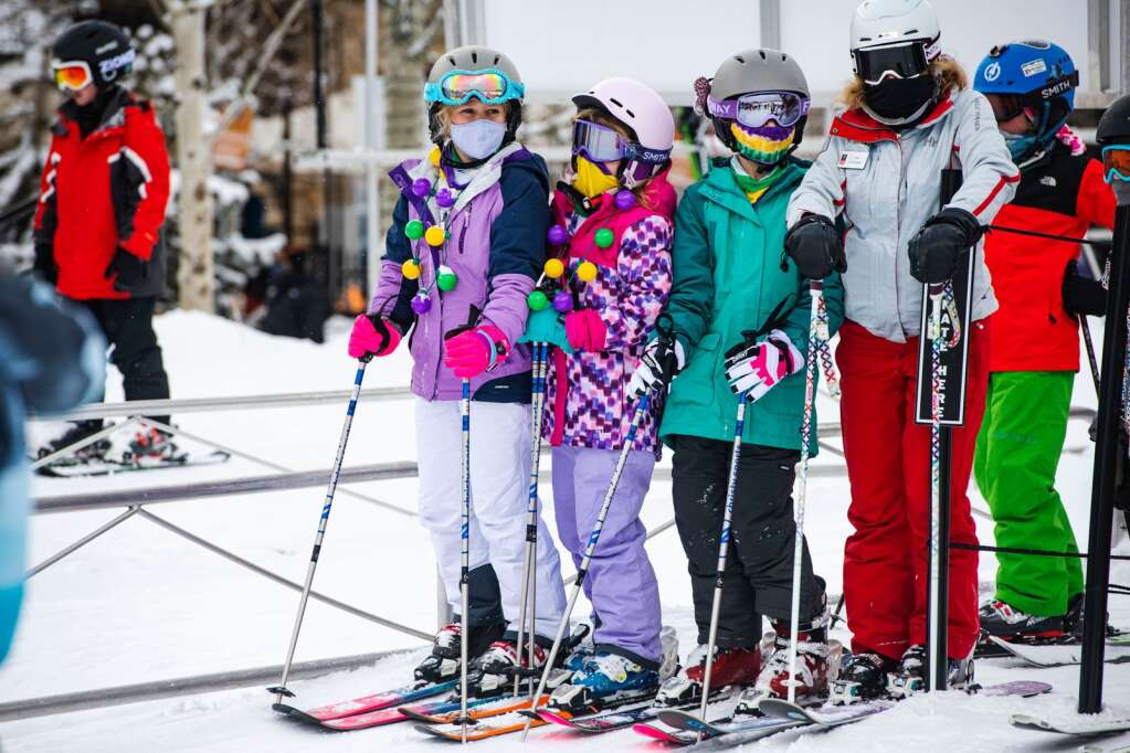 Little skiers wait in line with Mardi Gras beads to load onto the Village Express lift in Snowmass on Tuesday, Feb. 16, 2021. (Kelsey Brunner/The Aspen Times)