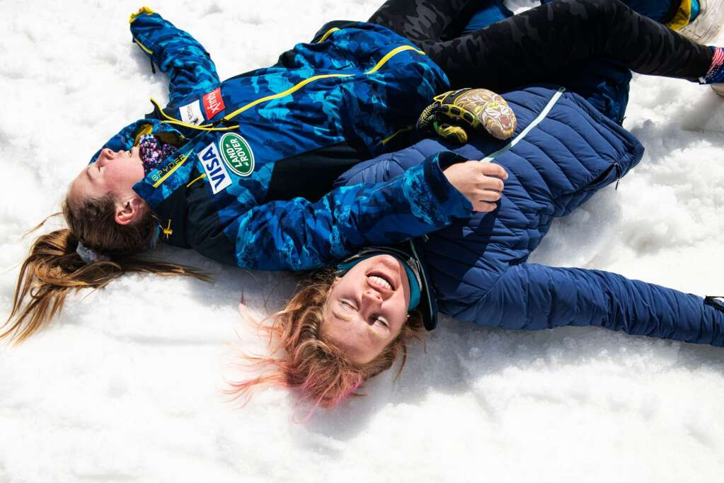 Alpine skiers AJ Hunt, left, and Tricia Mangan lay on the ground catching their breath after having a wrestling match at the end of the Women's Slalom National Championships at Aspen Highlands on Friday, April 16, 2021. (Kelsey Brunner/The Aspen Times)
