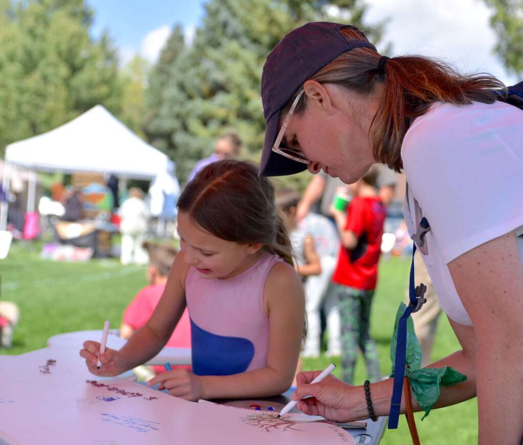 Ella Eperjesi, left, and Allison Jurgens work on their messages to first repsonders as part of the first annual Art in the Park on Saturday, Sept. 3, 2021, at Polhamus Park in Granby.   Amy Golden/Sky-Hi News