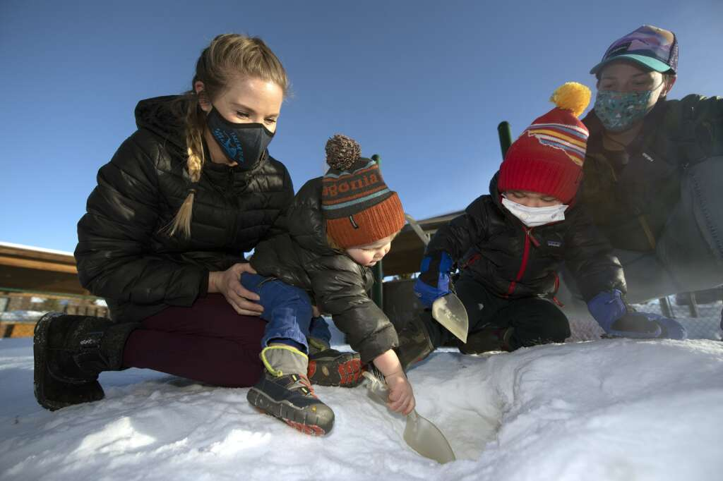 Timberline Learning Center teachers Sarah Young, left, and Leah Tharp watch Fischer and Forest Dineen explore on the school playground in Breckenridge on Friday, Jan. 8. | Photo by Jason Connolly / Jason Connolly Photography