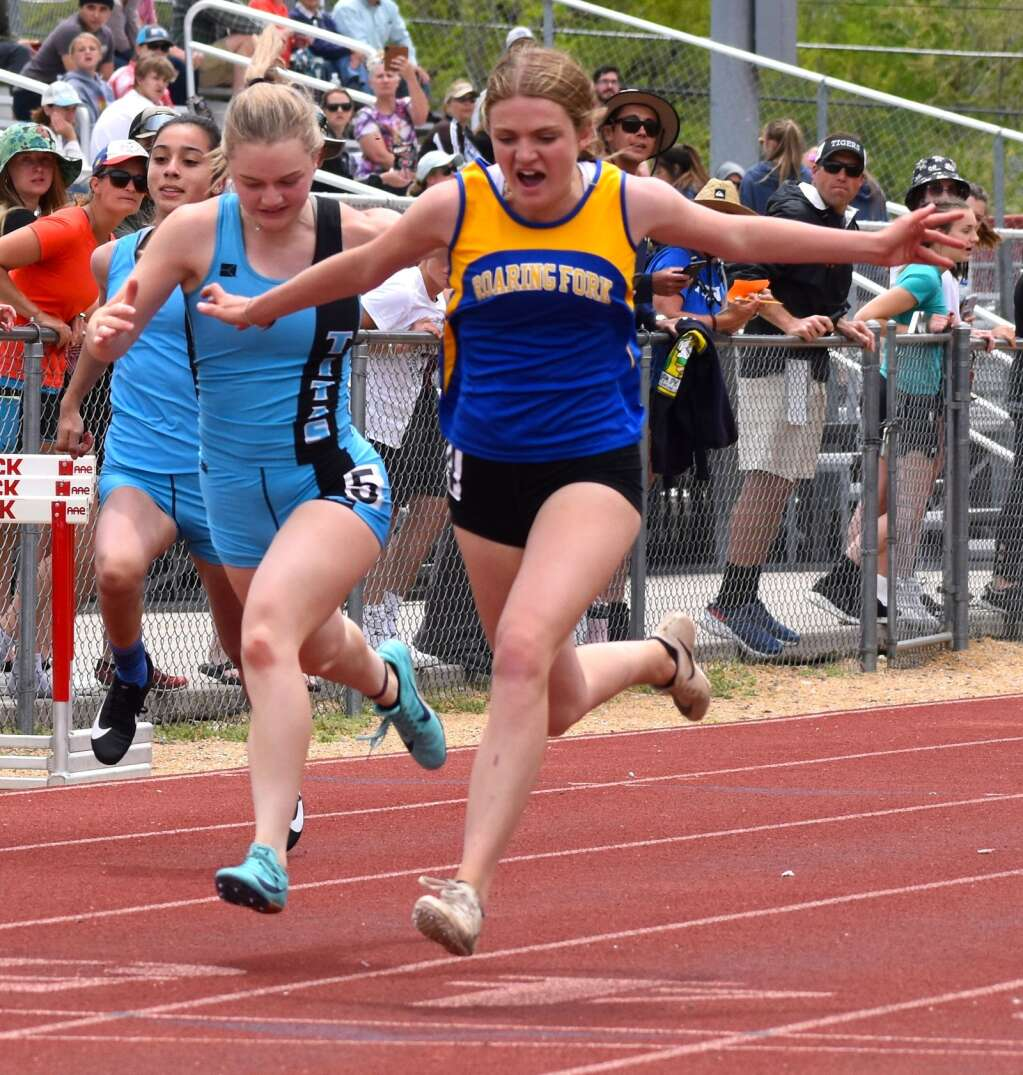 Roaring Fork's Lily Nieslanik leans for the 100-meter win Saturday over Coal Ridge's Railey Largent.| John Stroud/Post Independent