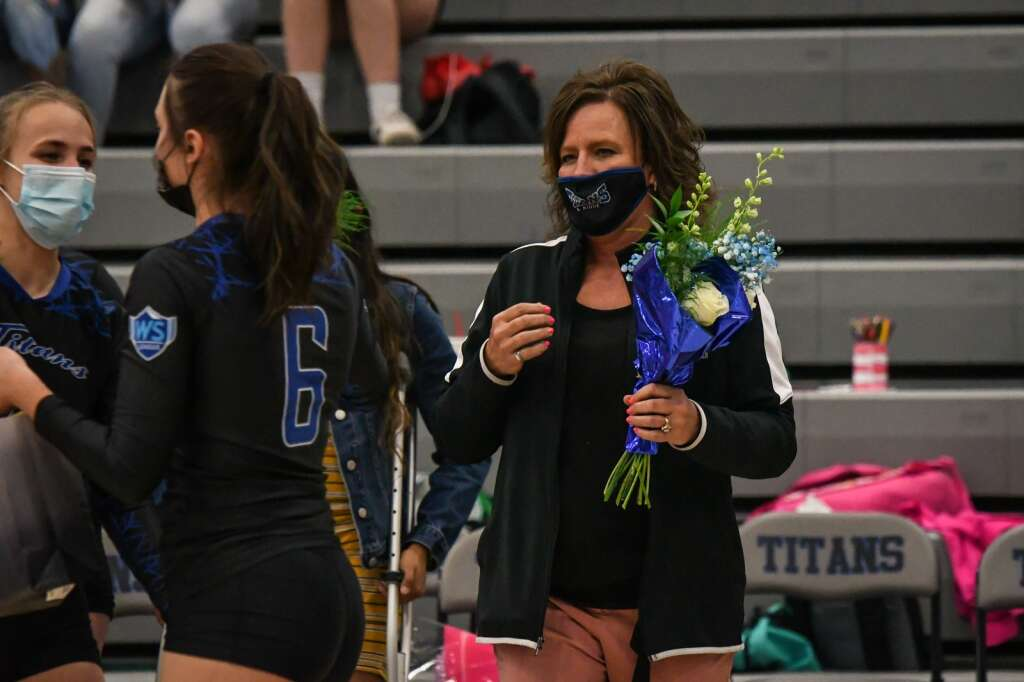Coal Ridge Volleyball Coach Aimee Gerber holds flowers for seniors during the senior night ceremony before the start of last week's game against Rifle. |Chelsea Self / Post Independent