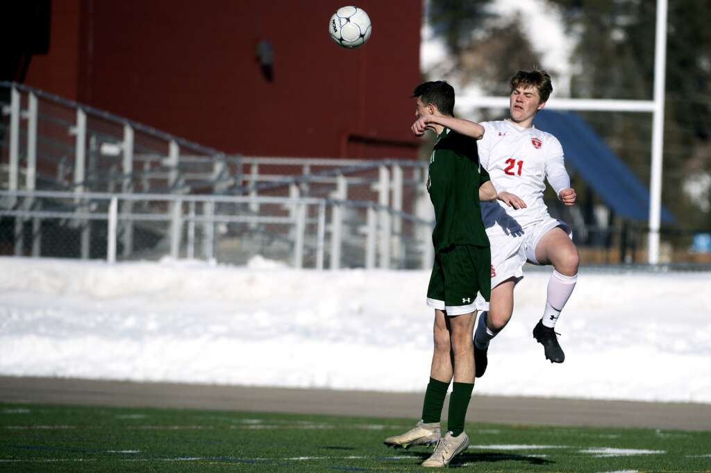 Summit High Tiger Colin Doran goes up against Steamboat Springs Sailor John Reece for a header during the home opener of the boys varsity soccer season at Climax Molybdenum Field at Tiger Stadium on Thursday, March 18, 2021. The Tigers lost to the Sailors 3-0. | Photo by Jason Connolly / Jason Connolly Photography