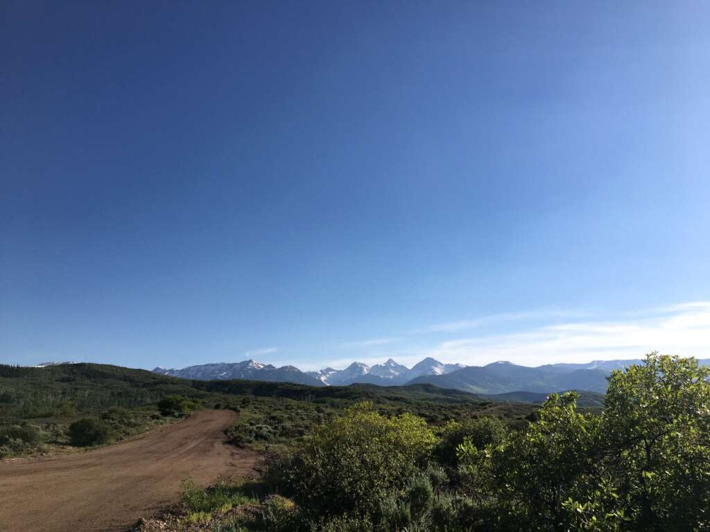 A road connecting the Cougar Canyon and Cozy Point Ridge subdivisions in Snowmass Village boasts sweeping views of peaks in the Elk Range. Snowmass Town Council toured the mostly undeveloped land during a site visit on Monday, June 7, 2021.    Kaya Williams/The Snowmass Sun