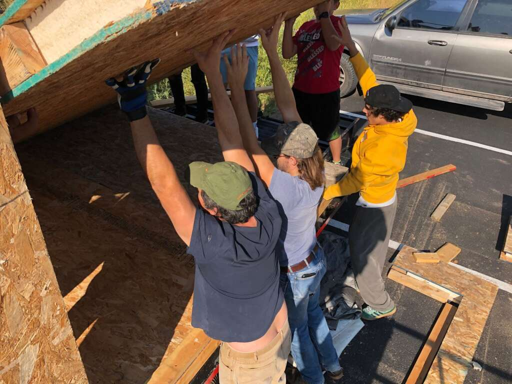 Instructor Edgar Rojo (left) and students in his woods/construction class raise a structural insulated panel Sept. 7 on the tiny home they are building. | Scott Condon/The Aspen Times