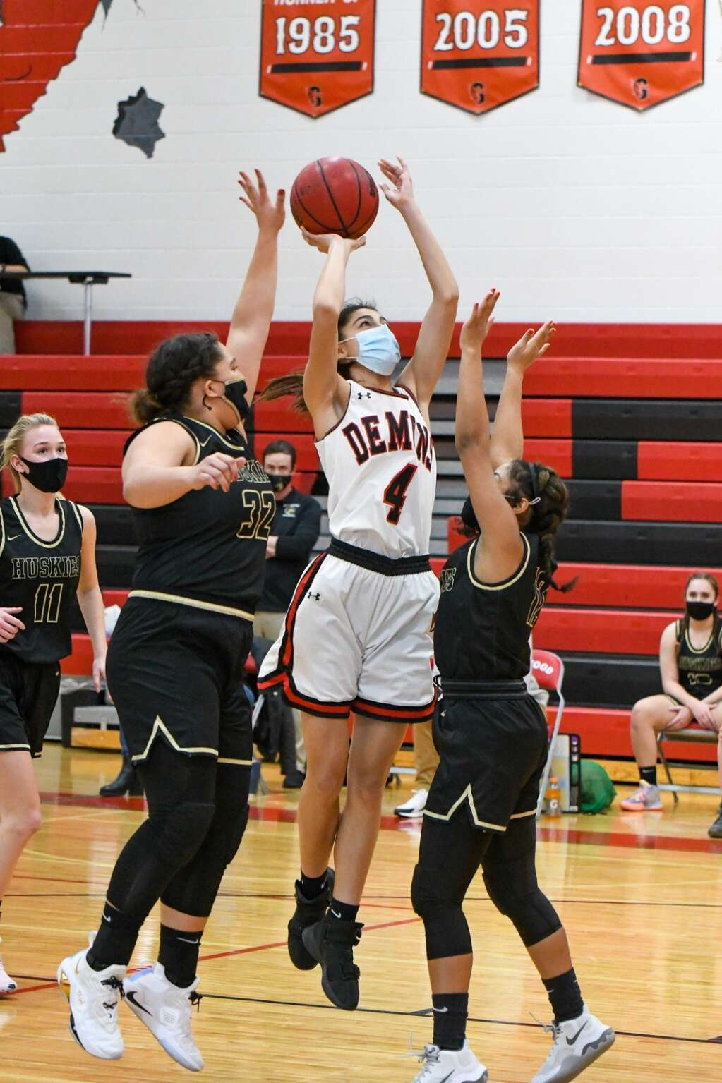 Glenwood Springs Demon Miah Suarez leaps through the defending Battle Mountain Huskies during Thursday night's home game. |Chelsea Self / Post Independent