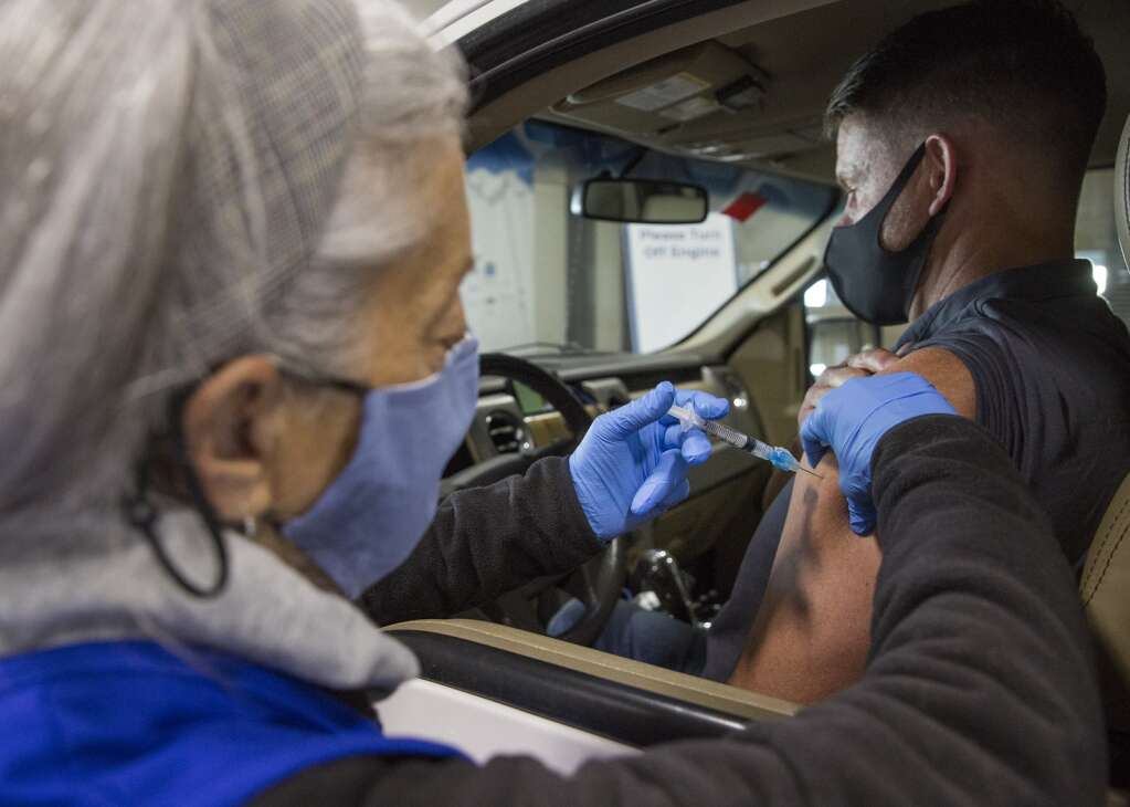 Sharon Gilbert administers the Moderna vaccine to a patient at the drive-thru vaccination location at the Utah Film Studios. Officials said more than 100 medically licensed professionals have volunteered to administer the shots. | Tanzi Propst/Park Record