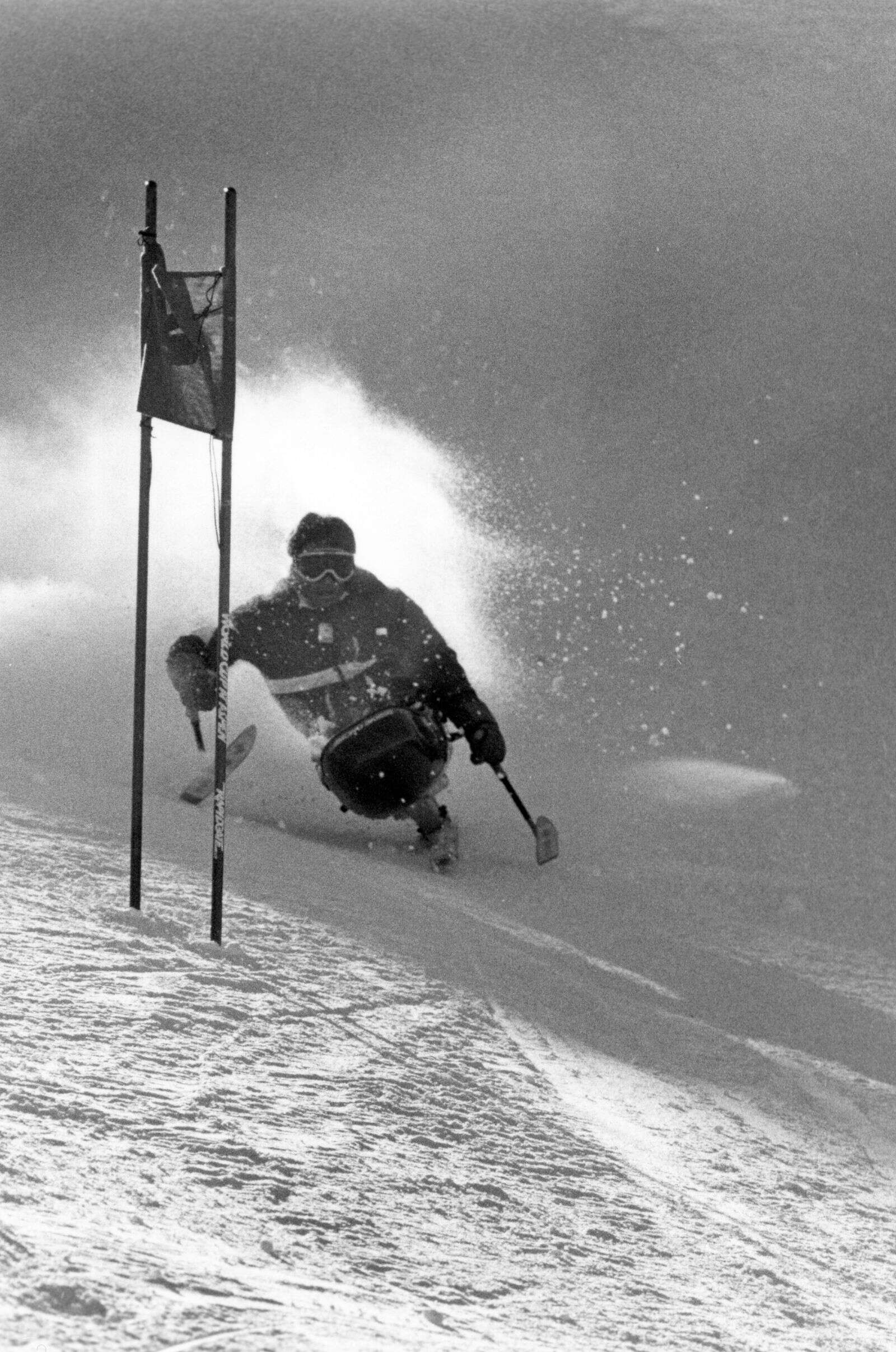 A person in a sit ski competes in the 1986 Rocky Mountain Regional Handicapped Races in Snowmass.