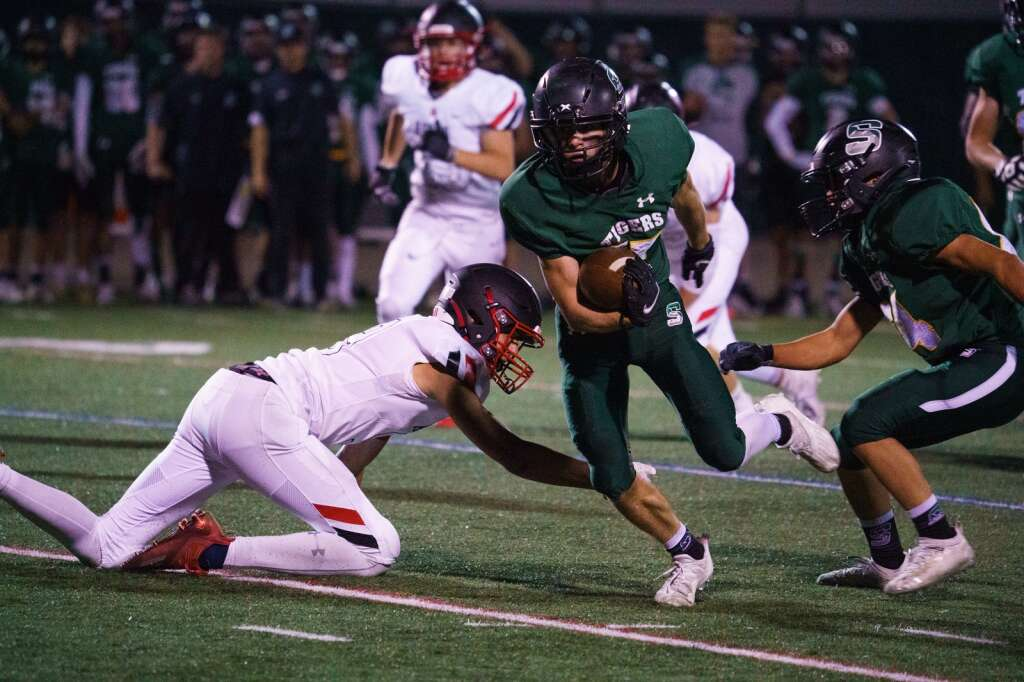Summit High School senior Aidan Collins spins away from a would-be tackler during the third quarter of the Tigers' 37-20 win over Aspen Friday, Sept. 10, at Tiger Stadium in Breckenridge. | John Hanson/For the Summit Daily News