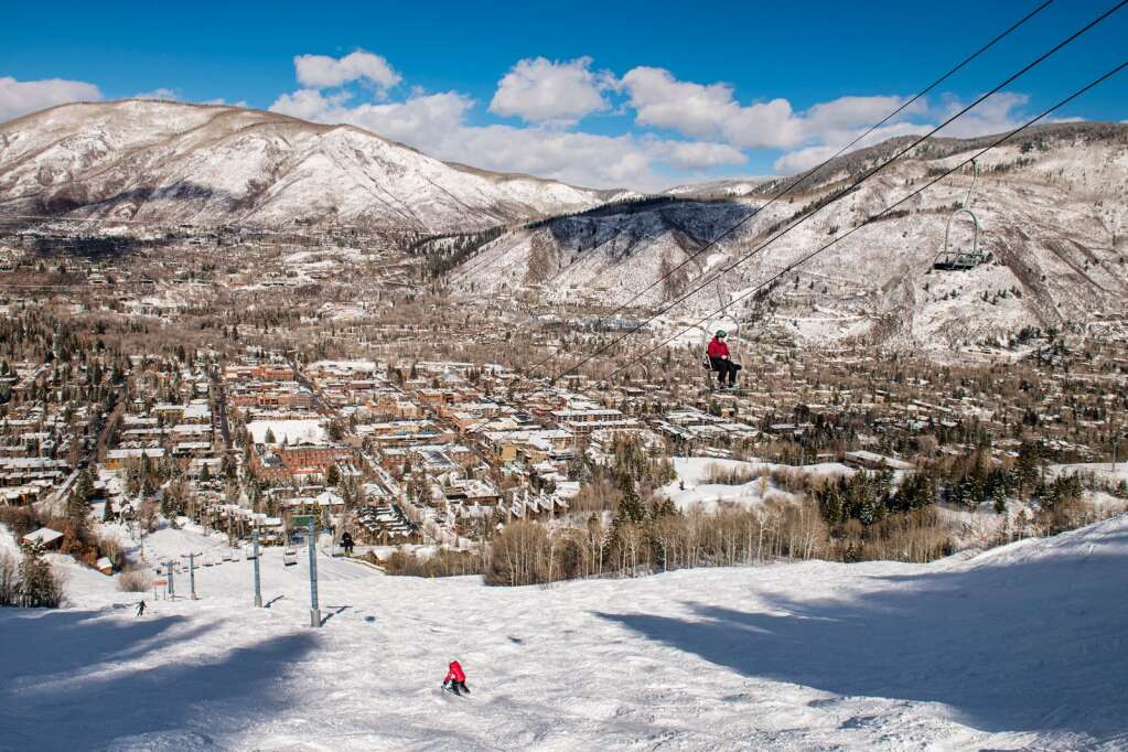 Skiers maneuver snowy moguls under Lift 1A in view of the town of Aspen on Thursday, Feb. 18, 2021. (Kelsey Brunner/The Aspen Times)