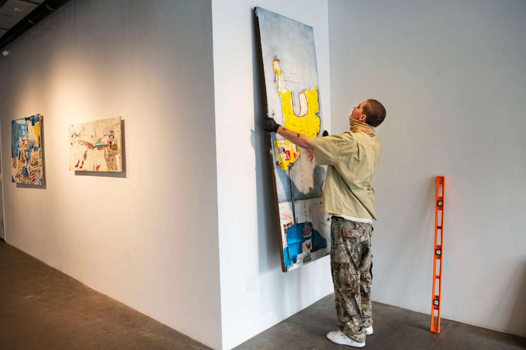 Axel Livingston, 19, hangs one of his pieces in the Gonzo Gallery for his first show in the space in Aspen on Tuesday, April 27, 2021. (Kelsey Brunner/The Aspen Times)