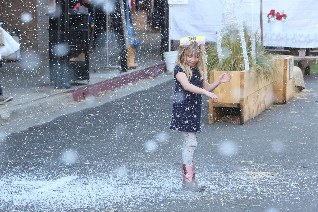 Five year old Harte Spiller takes a moment to admire the snowflakes falling in front of Stucki Jewelers in downtown Grass Valley Saturday. | Photo: Elias Funez