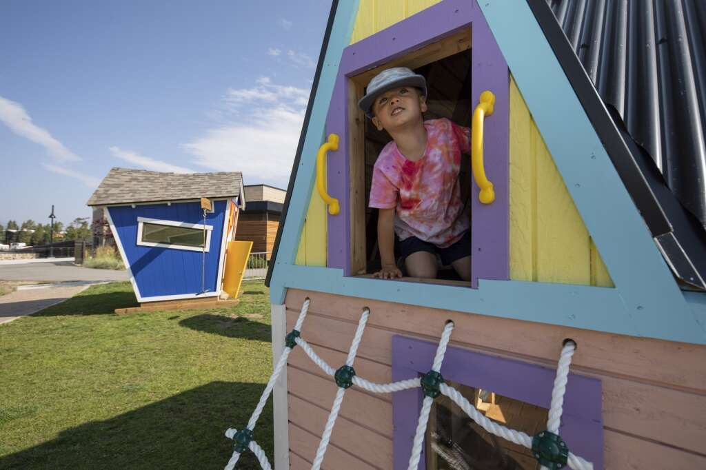 A child enjoys the Playhouse Project creations at the Marina Park in Dillon on Friday, Aug. 6. Each of the three playhouses will be auctioned off to raise money for Summit Habitat for Humanity.   Photo by Tripp Fay / Tripp Fay Photography.