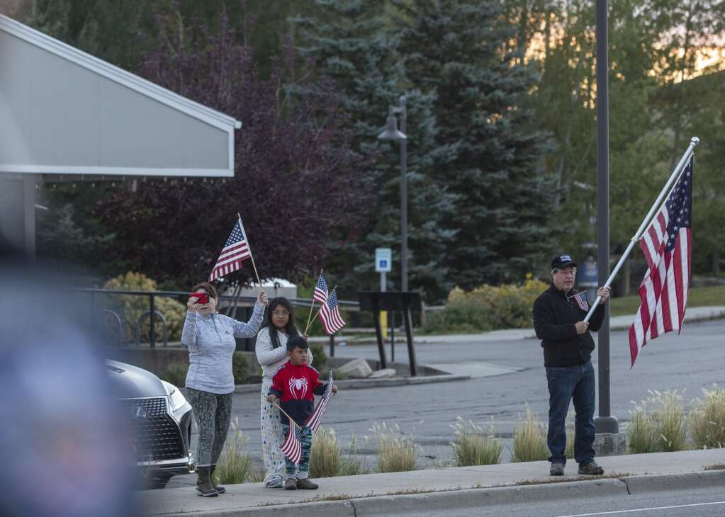 Passersby wave American flags from the sidewalk near Squatter's Brew Pub as the Park City Fire District Honor Guard carries the American flag down S.R. 224 Saturday morning. (Tanzi Propst/Park Record)