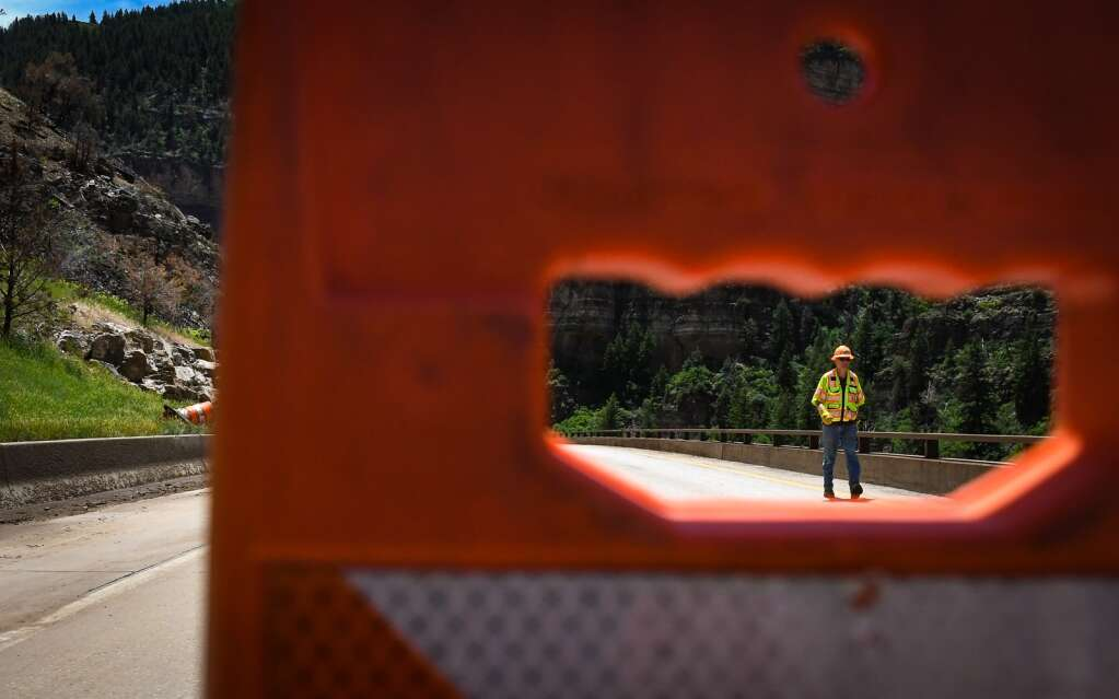A Colorado Department of Transportation Hydrologist walks down the closed westbound lanes of Interstate 70 on Monday after a mudslide swept down the cliffs in Glenwood Canyon in the area of the Grizzly Creek burn scar on Sunday. |Chelsea Self / Post Independent
