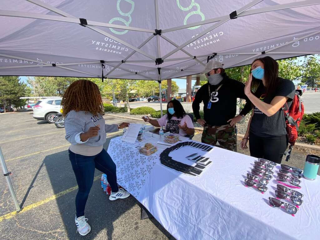 Sarah Woodson (in pink) manning a booth outside of Good Chemistry, a Denver-based cannabis cultivator and retailer, as part of a recent fundraising campaign. | Courtesy Good Chemistry