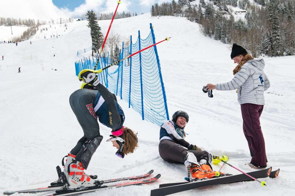American alpine skiers Ellis Morgan, left, demonstrates her crash as friend Tea Kiesel takes a break on the ground after the Women's Slalom National Championships at Aspen Highlands on Friday, April 16, 2021. (Kelsey Brunner/The Aspen Times)
