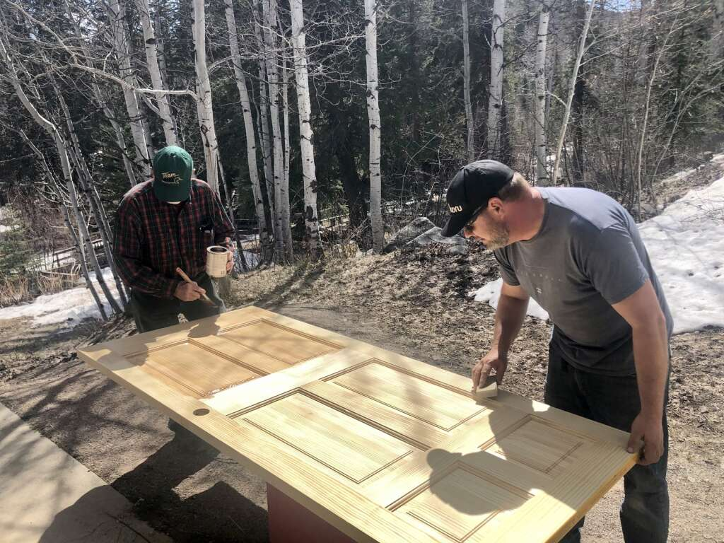 Craton Burkholder and Zeph Williams stain a wooden door outside the main lodge at the Aspen Camp for the Deaf and Hard of Hearing in Old Snowmass on April 11, 2021. | Kaya Williams/The Aspen Times