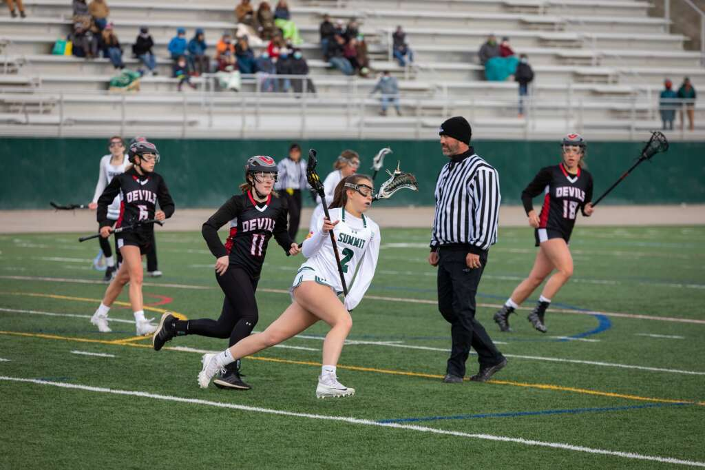 Chloe Nicholds craddles possession during the Summit High School varsity girls lacrosse team's 14-4 loss to Eagle Valley at Summit High School in Breckenridge on Tuesday, May 11, 2021. | Photo by Lucas Herbert / Lucas Herbert Media